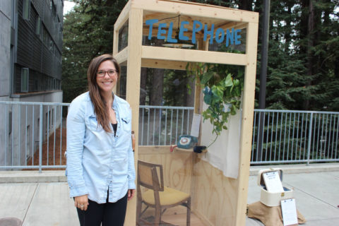 Photo of alumna Morgan Brown with phone booth.